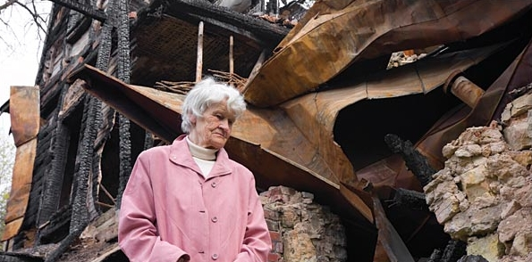 Older lady beside remains of home after a fire